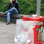 a red litter bin completely full with an additional plastic bag for trash next to it and a man sitting in the background in Hamburg Germany