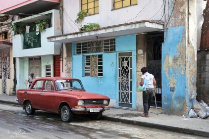 a woman walking in a street in la Havana Cuba on the side walk by a red parked car