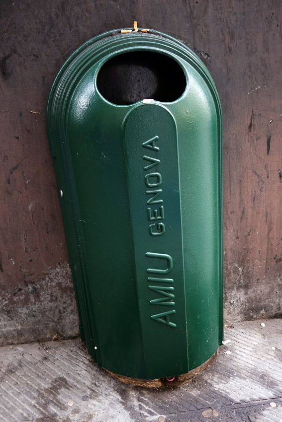 a green litter bin by the wall of a street in Genova Italy
