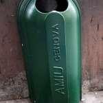 a green litter bin by the wall of a street in Genova Italy