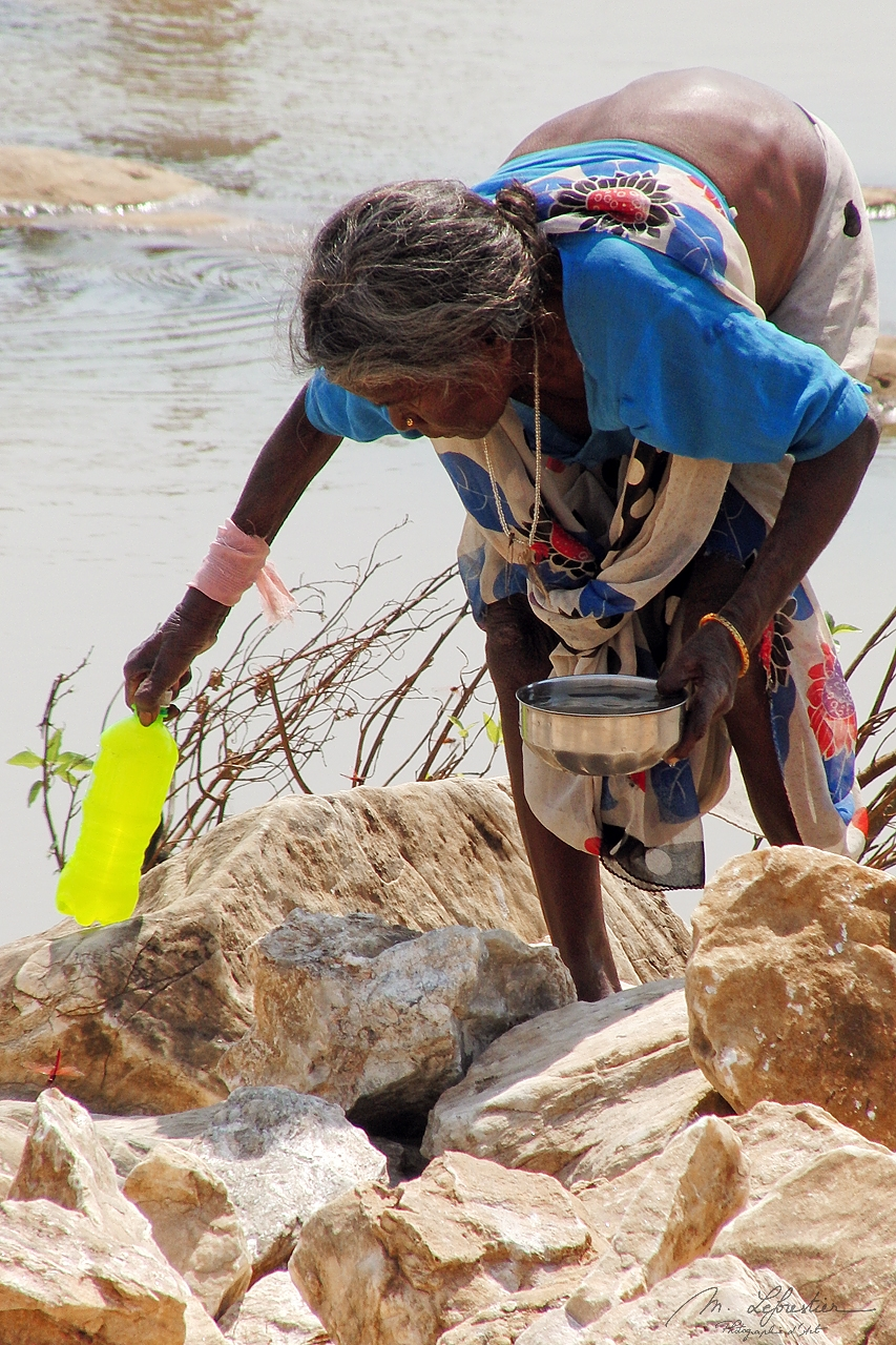 a local older woman is filing up a plastic bottle in the Narmada river at Marble Rocks in India