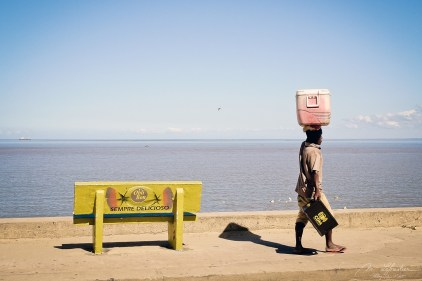 man walking pass a yellow bench and walking with a coolbox on his head in front of the Indian Ocean in Beira Mozambique