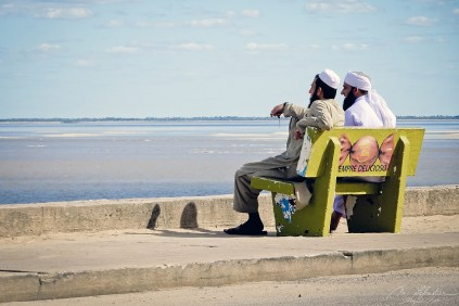 two muslim men sitting on a bench and watching the indian ocean in Beira Mozambique