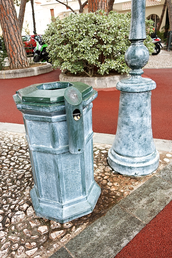 a green litter bin in the streets of Monaco city