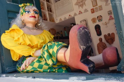 colorful dressed doll waring the colors of Brazil in the front of a store in the streets of Olinda