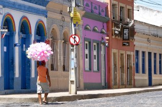man walking by colorful houses in the streets of Olinda in Brazil