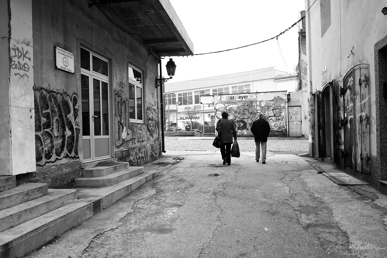 Two people walking in a street of Tuzla Bosnia photo in black and white