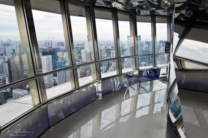 inside the tokyo tower at the top deck with Tokyo city view in the background