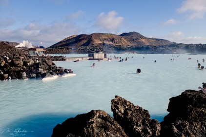 volcanic rocks at the Blue Lagoon in Iceland with people bathing in the hot springs