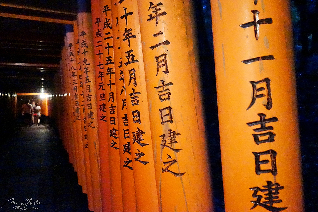 japanese inscriptions on the Torii gates of the Fushimi Inari Shrine in Southern Kyoto