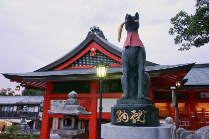 A statue of a fox holding a key in its mouth at the main gate of the Fushimi Inari shrine in Kyoto Japan