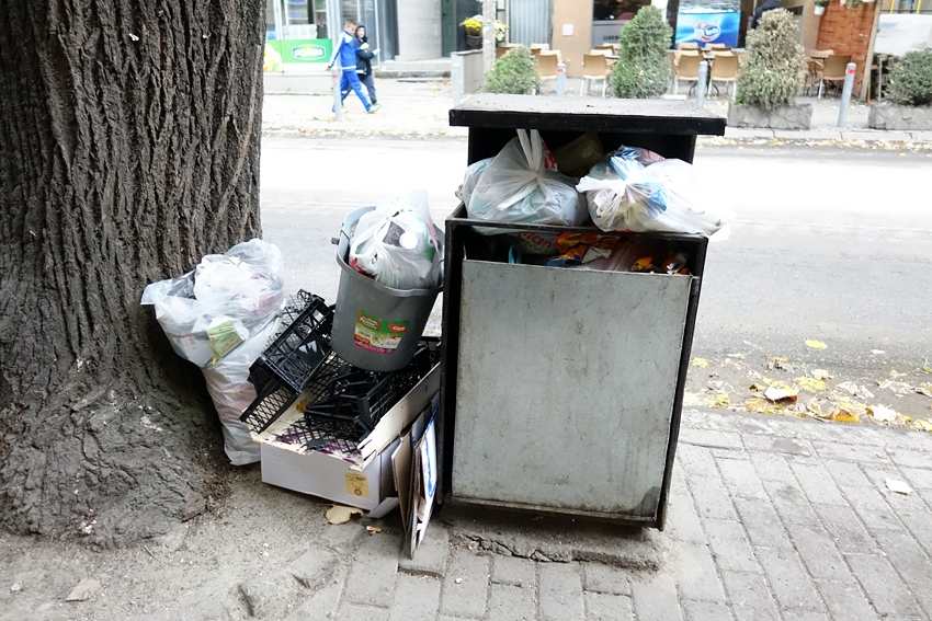 a very full litter bin with litter on the side by a tree in a street of Pristina Kosovo