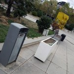 a litter bin in Pristina Kosovo with in the background a giant yellow lego on Ibrahim Rugova Square