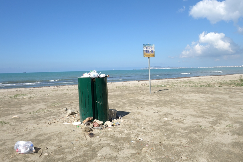 a green litter bin on the beach in Gorem in Albania