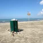 a green litter bin on the beach in Gorem in Albania