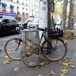 a bike is parked by a litter bin and a pole in Paris France during autumn