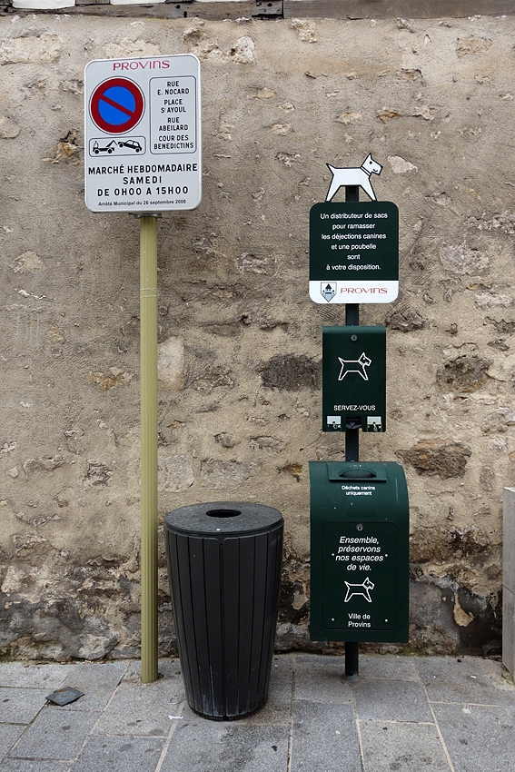 a street litter bin by a sign forbidden to park anda bin and bags for picking up dog poop in Provins UNESCO world heritage site in France