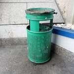 a green litter bin in a street corner, by the bus station in Zagreb Croatia