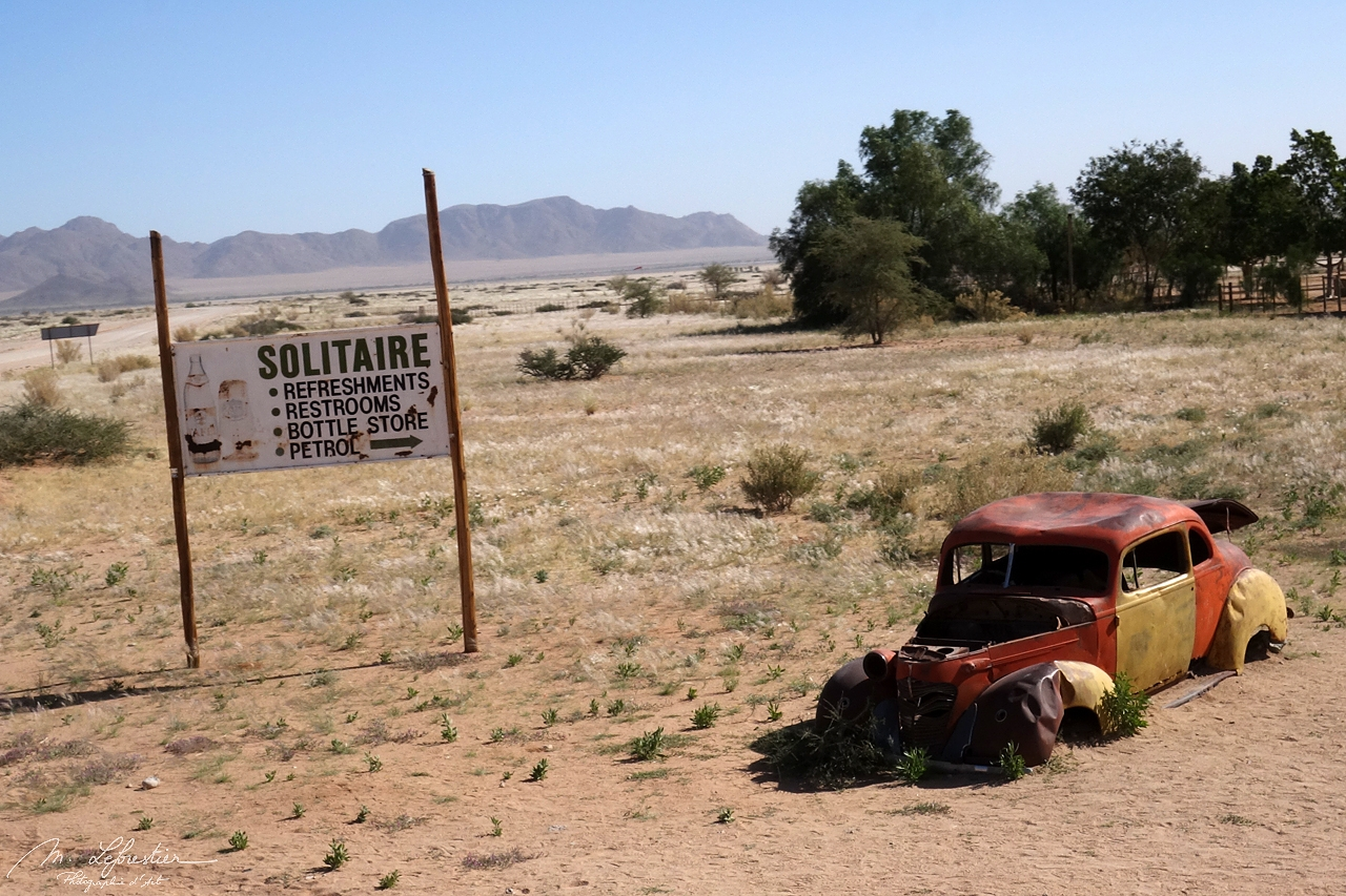 an old car by the Sign of Solitaire in the Namib desert