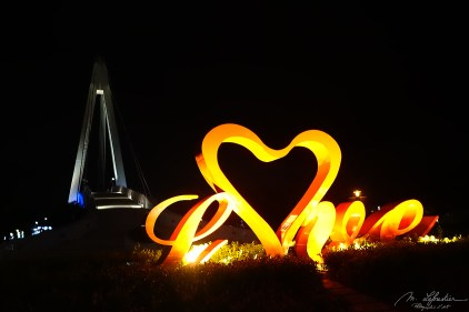 a sign of LOVE with the Lover bridge in the background in Tamsui fishermen's wharf just outside Taipei, Taiwan