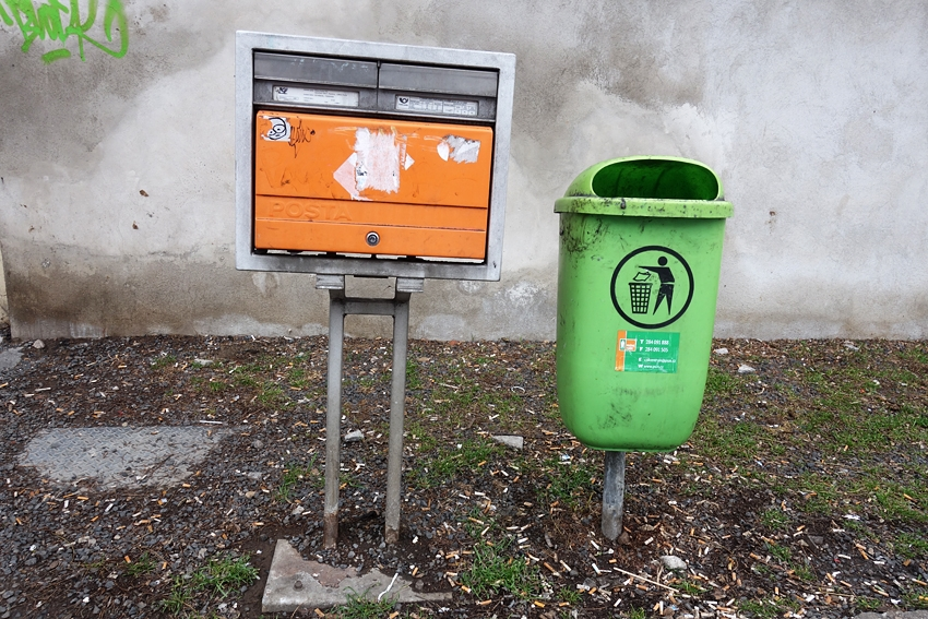 a green litter bin in the street in Prague Czech Republic by a mailbox