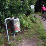 a tagged litter bin by a bicycle path in Mierlo the Netherlands, with a cyclist passing by