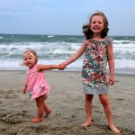 Sisters getting their picture taken on the beach.