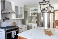 Home design choice: gray subway backsplash with quartz countertops and wine rack with in cabinet lighting
