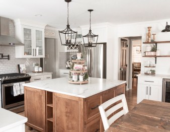 Home designed with Large custom wood island in white kitchen