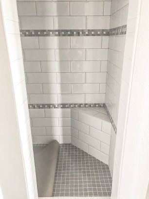 Home design selection is large subway tile with gray natural stone accent