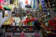 Inde, Mandawa, Novembre 2013. J'arrive à Mandawa à la tombée de la nuit et à peine la moto posée je repars explorer la rue principale de la ville. Les négociants sont, comme souvent, assis au milieu de leurs marchandises, ce qui donne vraiment une impression d'abondance. Pour autant, ils vendent tous la même chose, et ne voit pas souvent le chaland acheter ces petits jouets en plastique rouge ou ces sachets de cacahuètes. Mais va savoir, sur un malentendu…