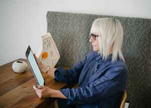 blond old woman reading book on tablet
