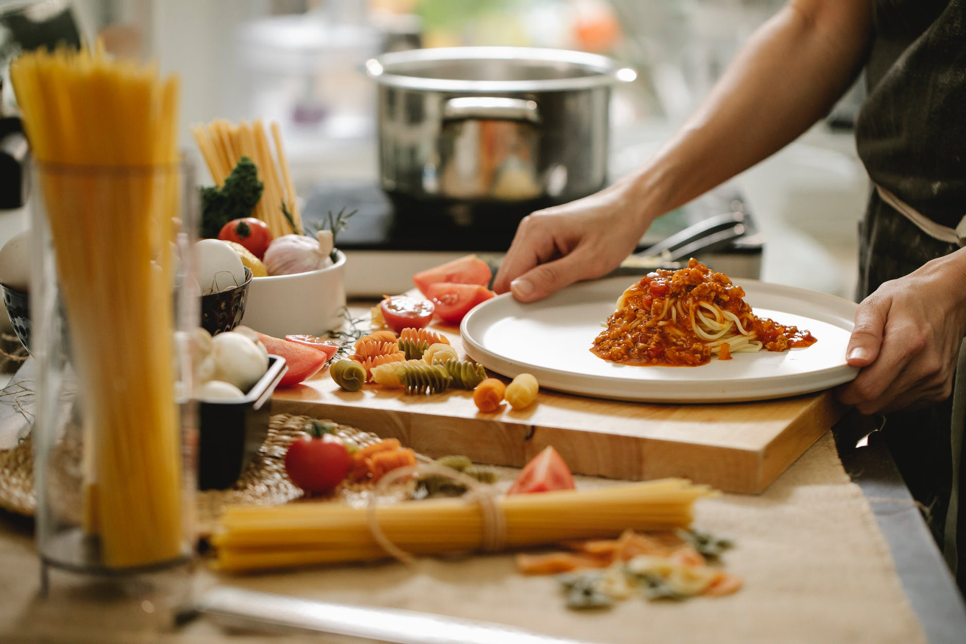 person cooking pasta with meat and tomatoes
