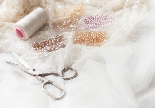 Close up of scissors, beads and thread on white bridal cloth