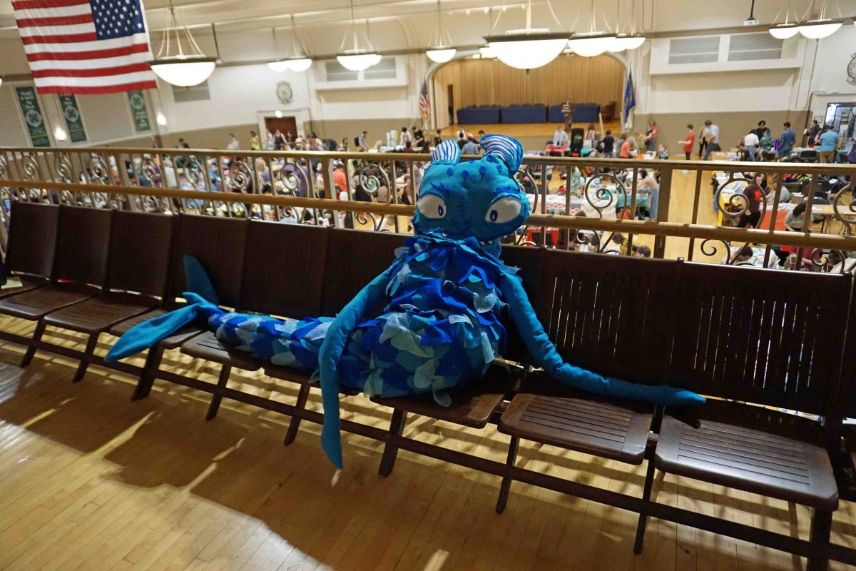 Picture of the Chicago Zine Fest 2019 mascot, a light blue Lake Michigan Sea Serpent, the size of a person sitting up on and laying across several chairs on the balcony of the Plumbers Union Hall in Chicago, IL. This serpent came alive from 2019's official poster created by Neil Brideau. Artist Rachel McPadden designed the display based on Neil's poster art, as seen in the storefront window of Quimby's Bookstore before the fest.