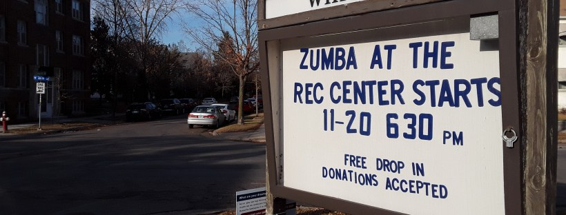 Large wood-framed outdoor sign at Whittier Park, Minneapolis, MN, announcing Zumba class starting November 20, 2019 at 6:30 pm.