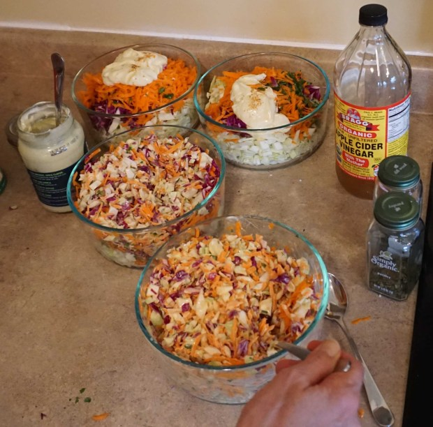 Picture of colorful coleslaw containing light green and red cabbage, orange carrots, dark green parsley, mayonnaise, apple cider vinegar, and some ground up hot pepper to taste.