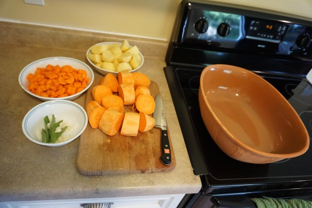 Photo of suggested ingredients to cook with a chicken in a clay pot. Peeled potatoes cut into large chunks are shown in a large bowl on a counter top along peeled chunks of sweet potatoes on a cutting board and bite size chunks of peeled carrots in another bowl. About six fresh sage leaves and 10 small peeled and halved cloves of garlic are shown in a third bowl. On the stove top next to the counter top, the bottom half of the clay pot is visible.