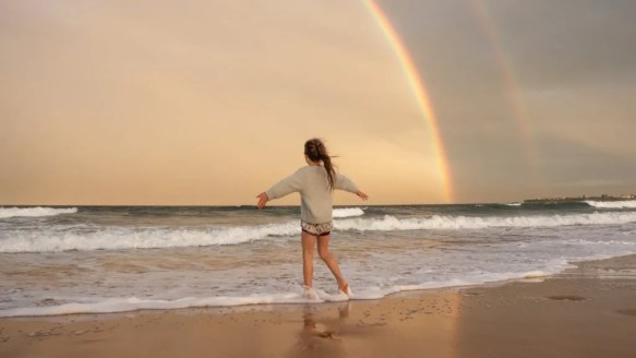woman on beach with rainbow, divine love is all around us