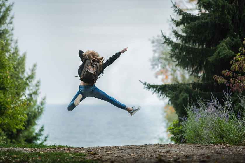 woman jumping wearing green backpack, excitement in the spiritual journey
