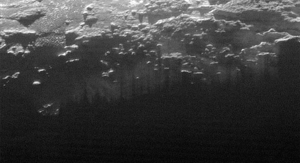 La puesta del sol ilumina la niebla cercana a la superficie, donde se proyectan las sombras de colinas y pequeñas montañas.