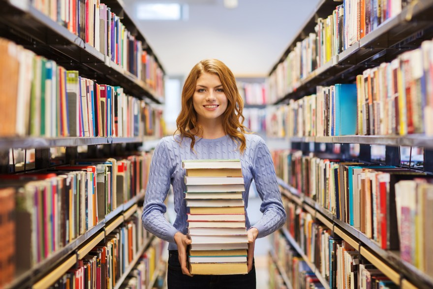 happy student girl or woman with books in library