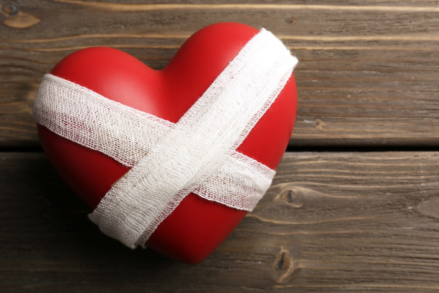 Bandaged heart on wooden background