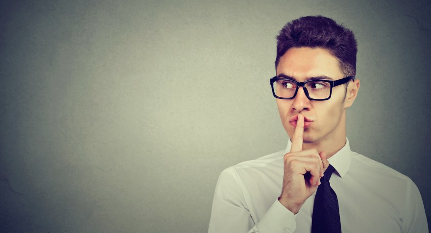 Secret guy. Man saying hush be quiet with finger on lips gesture looking to the side isolated on gray wall background.