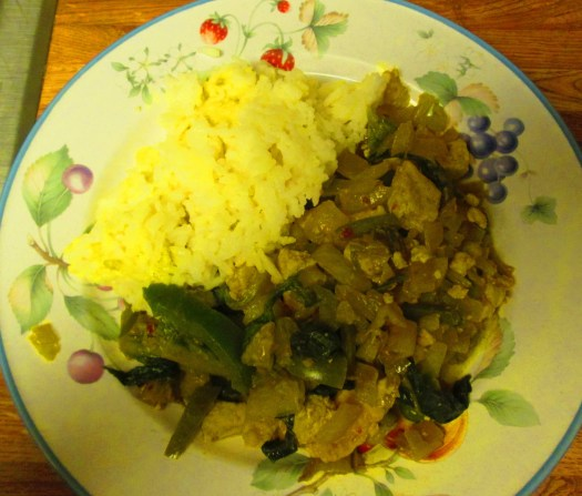 This stir fry dish has tofu, green bell peppers, onions, and romaine lettuce with white rice on the side.