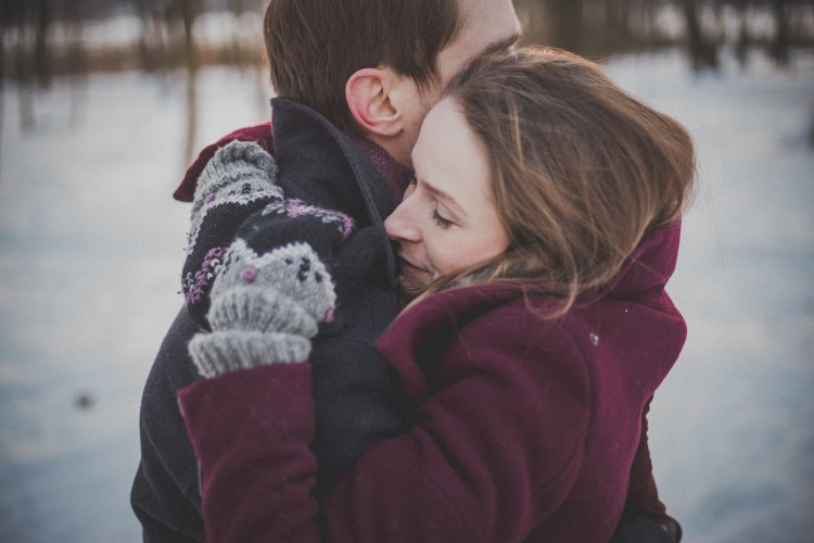 couple on engagement session with a passionate hug on the snow