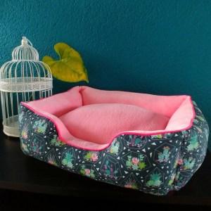 Panier au tissu extérieur bleu foncé avec des cactus entouré d'un dôme de verre et un tissu intérieur rose bonbon