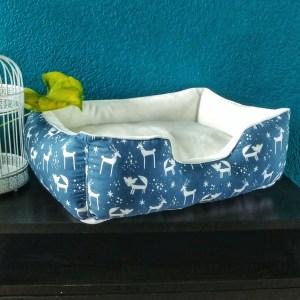 Panier pour chats avec tissu intérieur blanc et tissu extérieur bleu à motif de cerfs et de renards blanc, bleu clair et or
