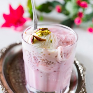 Rose falooda a cooling summer dessert which is rich and delicious. It's made with milk rose syrup chia seeds and falooda vermicelli and topped with a variety of toppings
