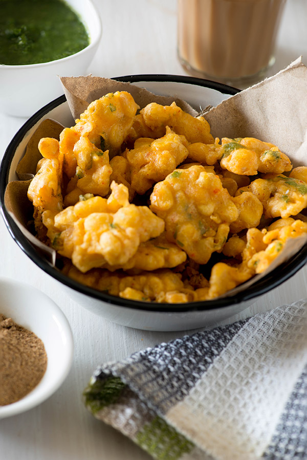 Corn Pakoda is a delicious teatime snack or Indian starter dish. Corn Pakora is an easy recipe in which deep-fried crisp corn fritters are made with chickpeas flour, sweet corn and regular Indian spices. As rainy season is about to arrive and we are already having few showers here and there. In India, we are conditioned to celebrate rains with some hot pakoras with a steaming cup of masala chai when it is pouring
